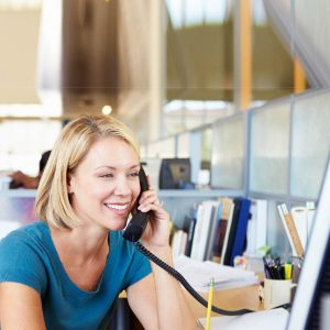 smiling woman talking on phone in office